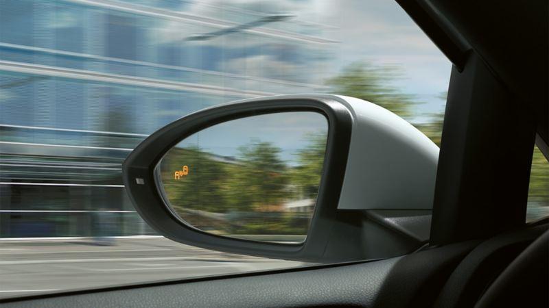 """Linker Außenspiegel vom Fahrerplatz aus gesehen mit leuchtendem Symbol des """"Blind Spot""""-Sensors"""