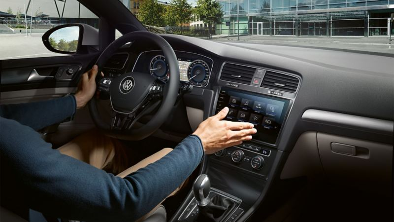 A man sits in a VW Golf and controls the on-board computer using a hand movement