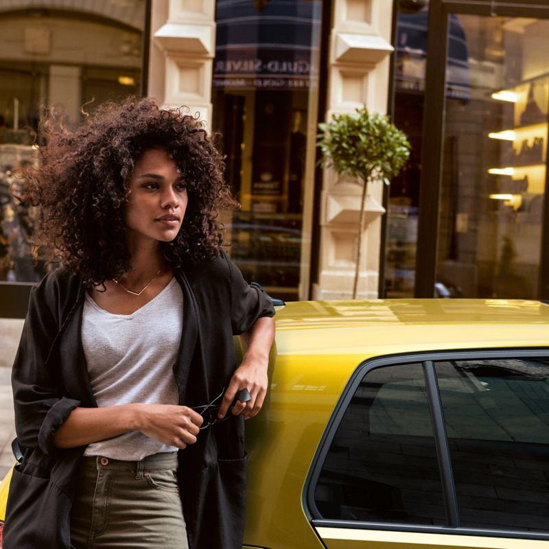 Frau lehnt gegen einen parkenden VW Golf