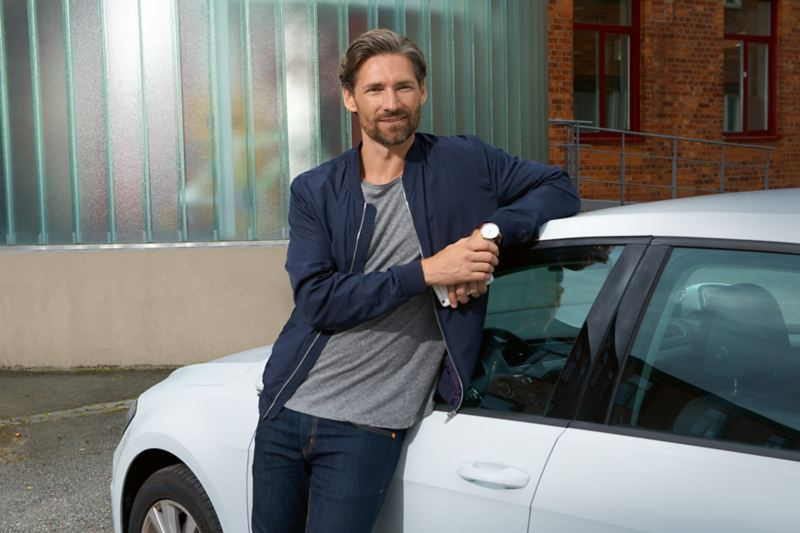 lächelnder Mann lehnt am VW Golf GTE