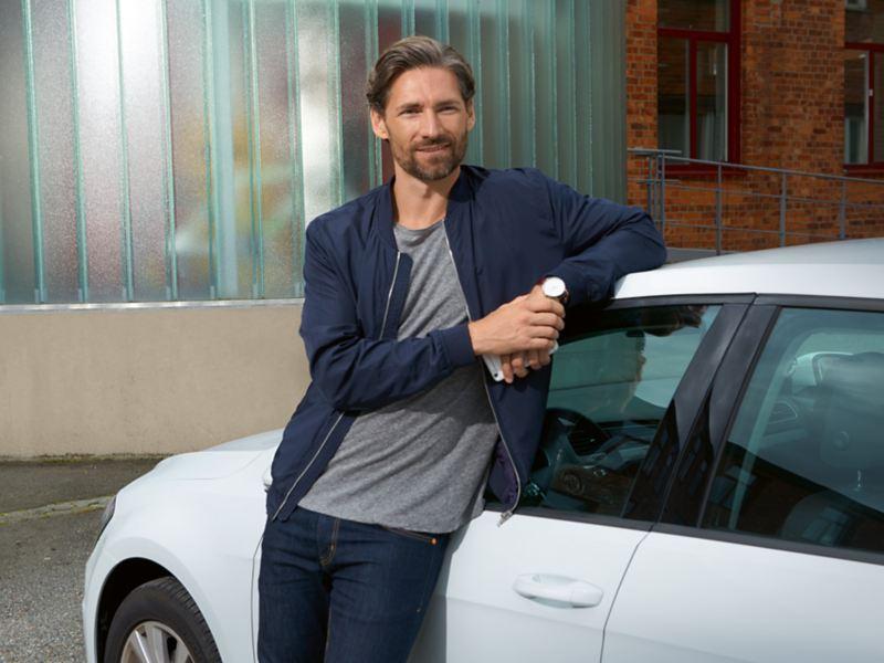 Uomo che sorride appoggiato a Volkswagen Golf GTE