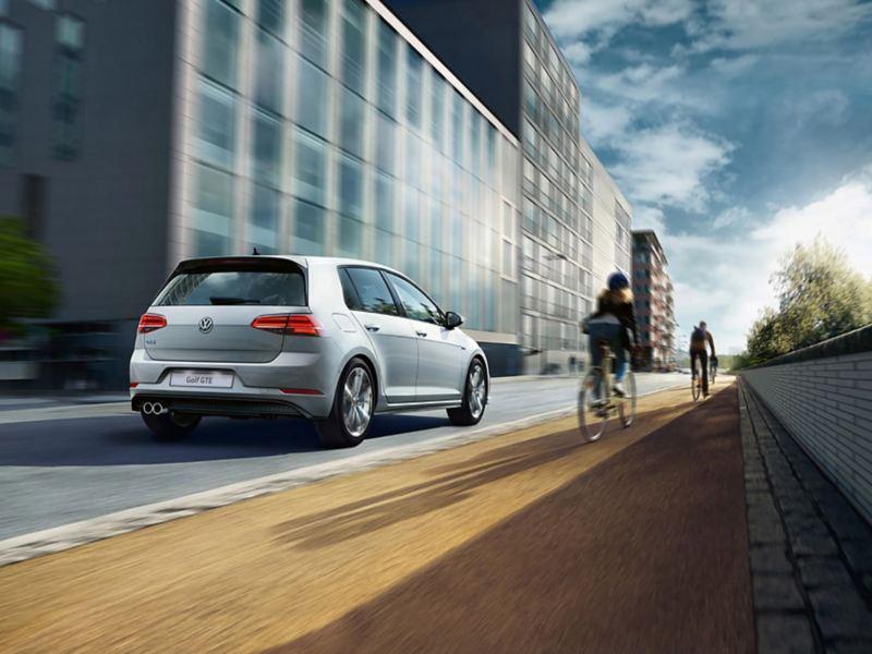 Volkswagen Golf GTE, vista posteriore, in marcia su strada, accanto un ciclista