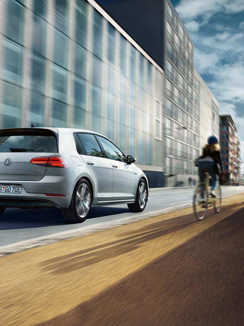VW Golf GTE Heckansicht fährt auf einer Straße, daneben Fahrradfahrer