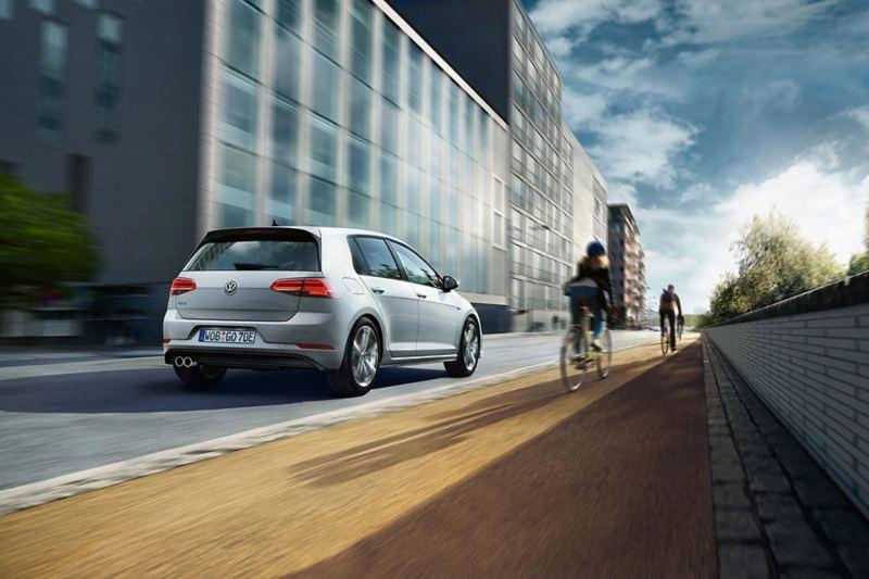 VW Golf rear view driving on a street, a biker next to it