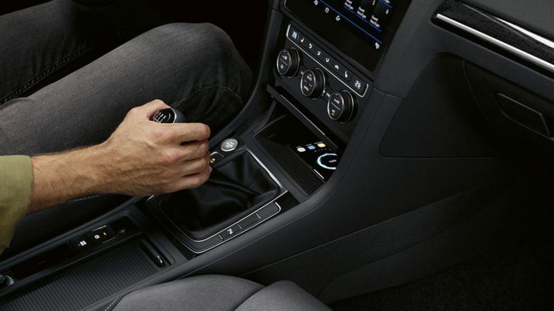 """Interni di VW Golf con interfaccia per telefono """"Comfort"""", la mano di un uomo è posizionata sulla leva del cambio"""