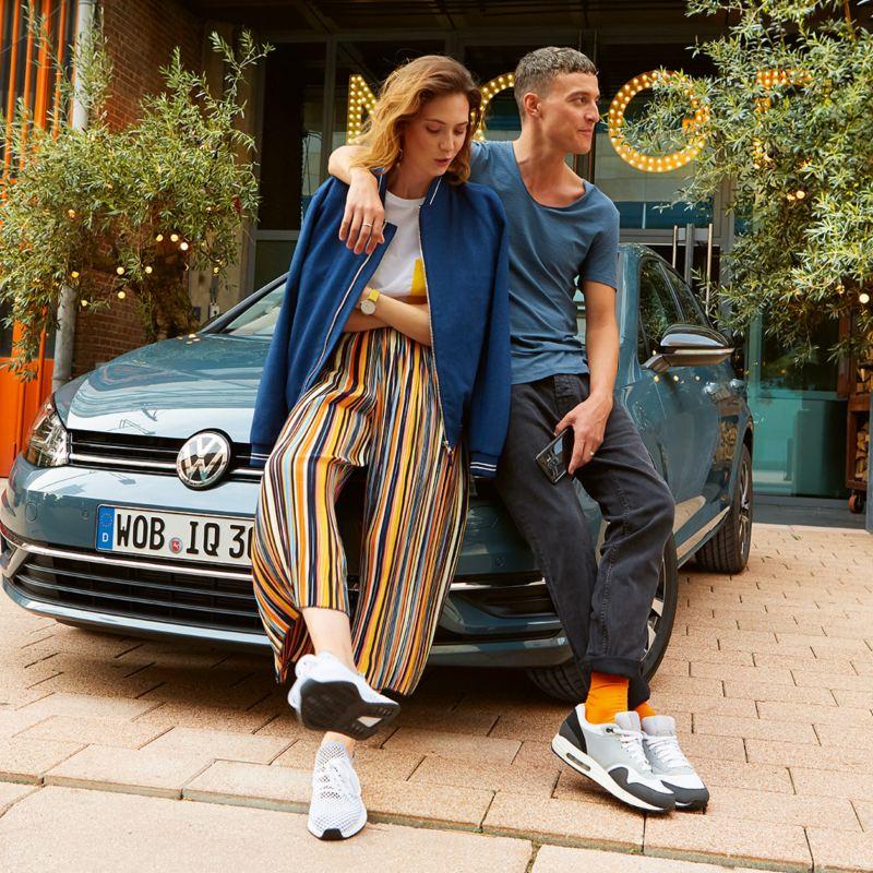 Personer sitter på panseret på Volkswagen Golf