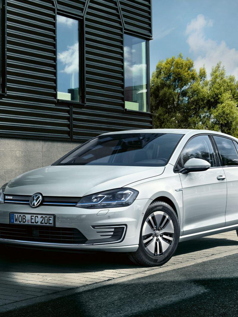 VW e-Golf parkt am Straßenrand, eine Frau mit Hund geht vorbei