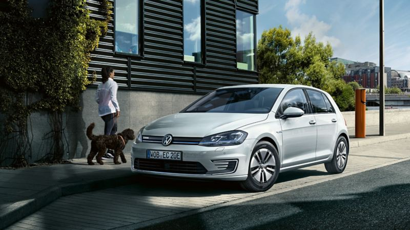 En kvinne går forbi en Volkswagen e-Golf med hunden