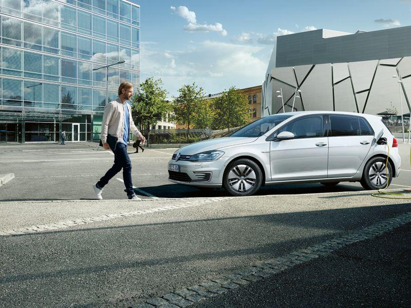 VW e-Golf Seitenansicht parkt am Starßenrand, angeschlossen an Ladesäule. Ein Mann läuft vorbei.