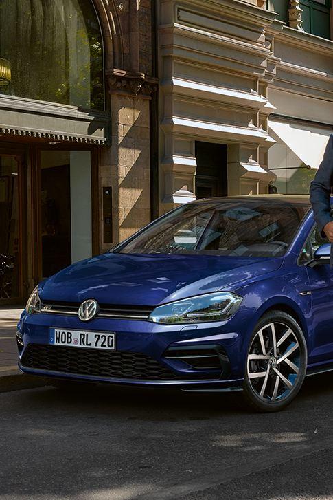 VW Golf im Vordergrund, ein Mann entfernt sich vom Auto