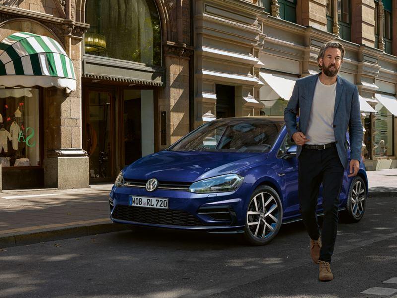 Sininen Volkswagen Golf kuvattuna kadun varrella, etualalla kävelee mies