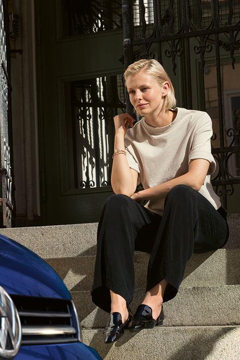 VW Golf parkt am Straßenrand, eine Frau sitzt auf einer Treppe