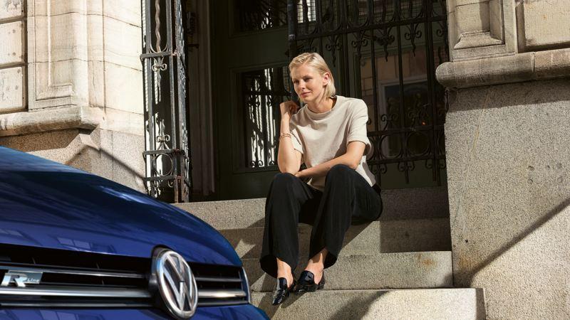 Nainen istuu talon edustan rappusilla ja katsoo kadulle parkkeerattua Volkswagen autoa