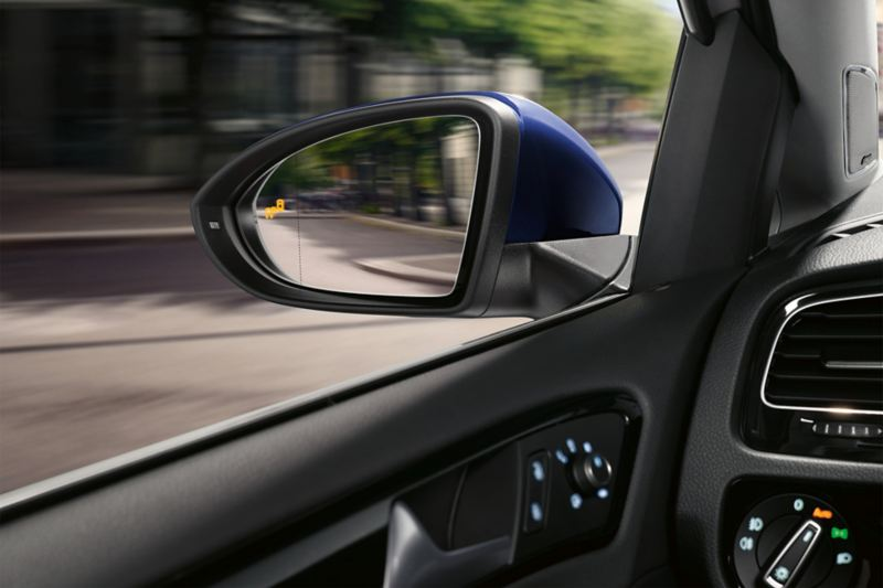 """outside mirror of a VW Golf TGI  with illuminated """"blind spot"""" symbol"""