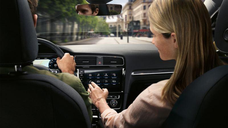 Fahrer und Beifahrerin im VW Golf Variant, Beifahrerin bedient das Navigationsgerät Discover Pro im Car-Net Menü
