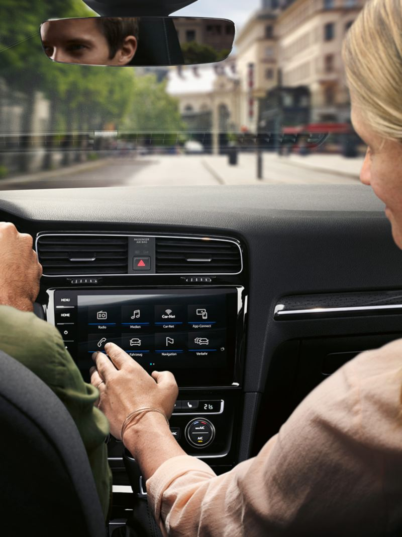 Driver and passenger in the VW Golf Estate, passenger operates the navigation system Discover Pro with Car-net menue