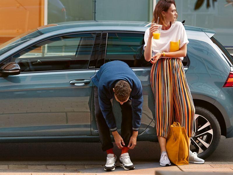 Blaugrauer VW Golf in Seitenansicht. Ein Mann und eine Frau lehnen sich an die Fahrzeugtüren.