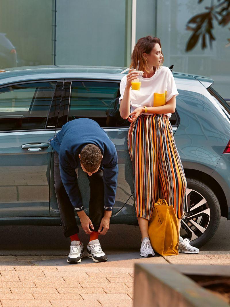 Paar steht neben blauem VW Golf.