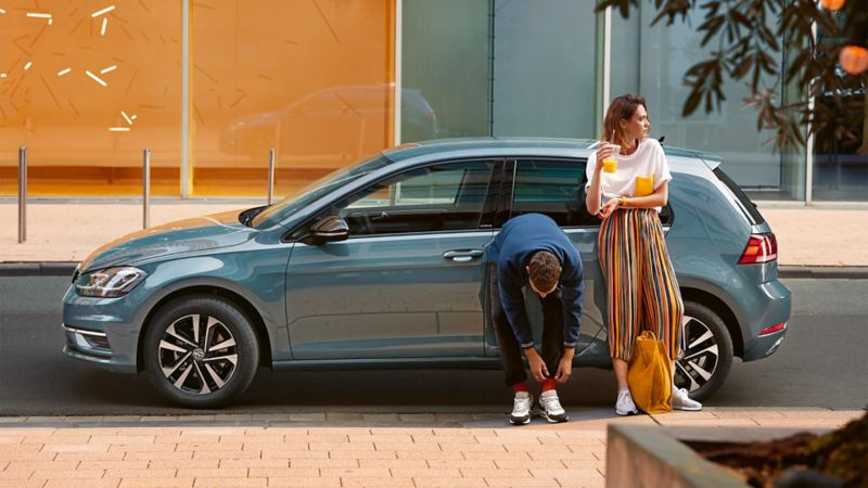 Ragazza e ragazzo appoggiati alla Golf Volkswagen