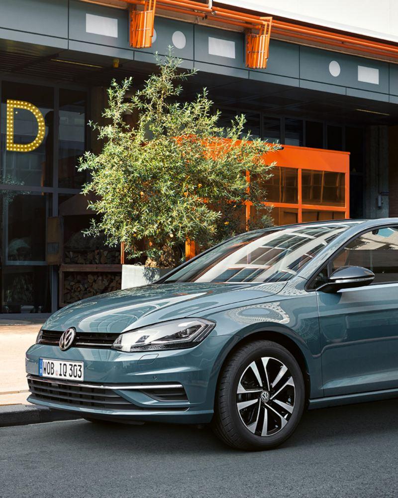 VW Golf IQ. Drive parkt vor einem Gebäude