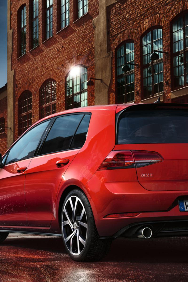 VW Golf GTI Performance parking on a road, man and women walking by