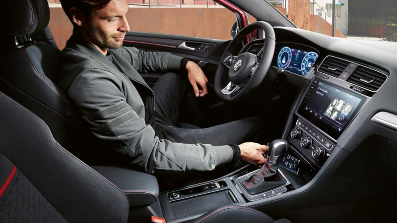 Man sitting in Golf GTI Performance with his smartphone