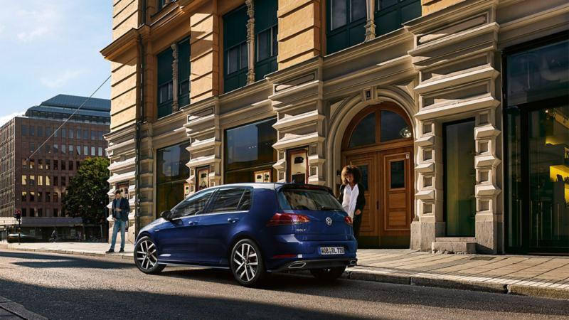 VW Golf von der Seite in der Stadt. Eine Frau nähert sich dem Auto von der Seite.