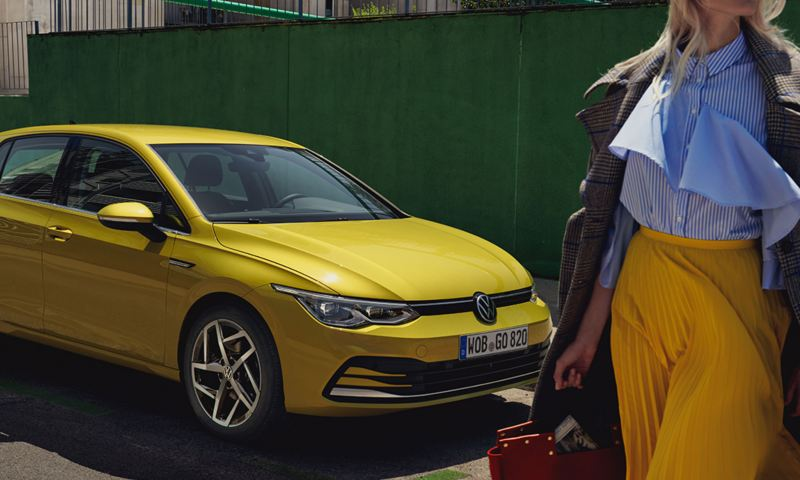 Woman stands in front of  VW Golf