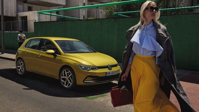 Volkswagen VW Golf sett fra siden på en vei foran en kvinne