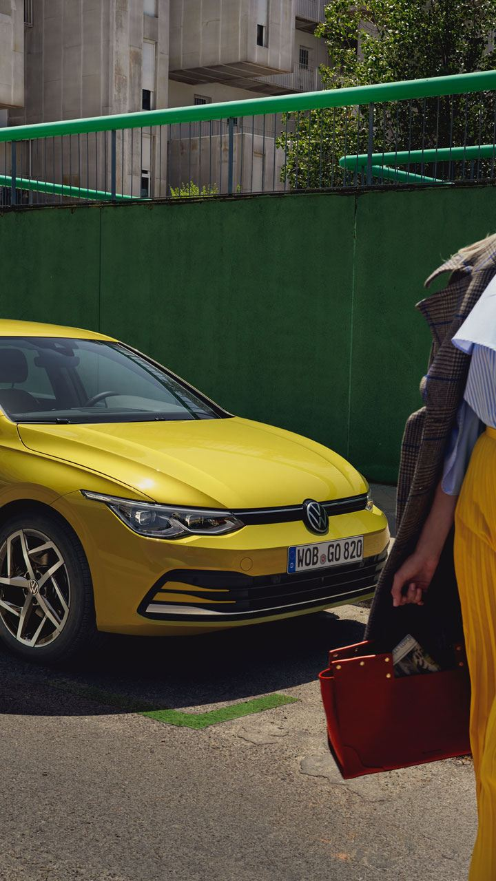 VW Golf side view is on a street, in front of a woman
