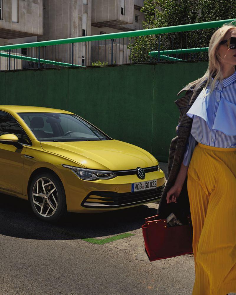 VW Golf Seitenansicht steht auf einer Straße, davor steht ein Pärchen und macht ein Selfie