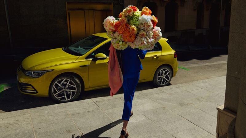 En kvinne med blomster går mot den nye Volkswagen Golf 8