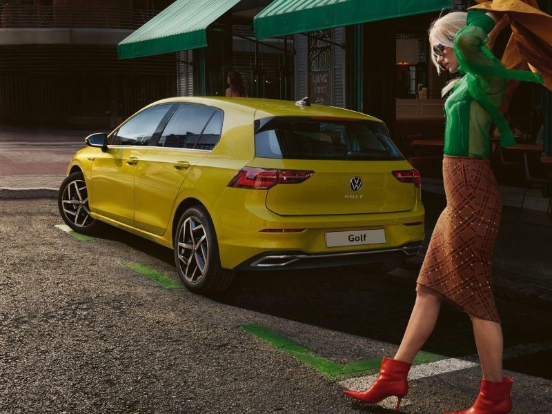 Una donna passeggia di fianco ad un'auto Volkswagen Golf 8