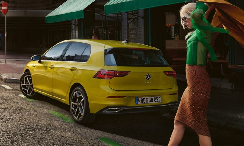 Rear view of the VW Golf, woman puts her coat in front of it