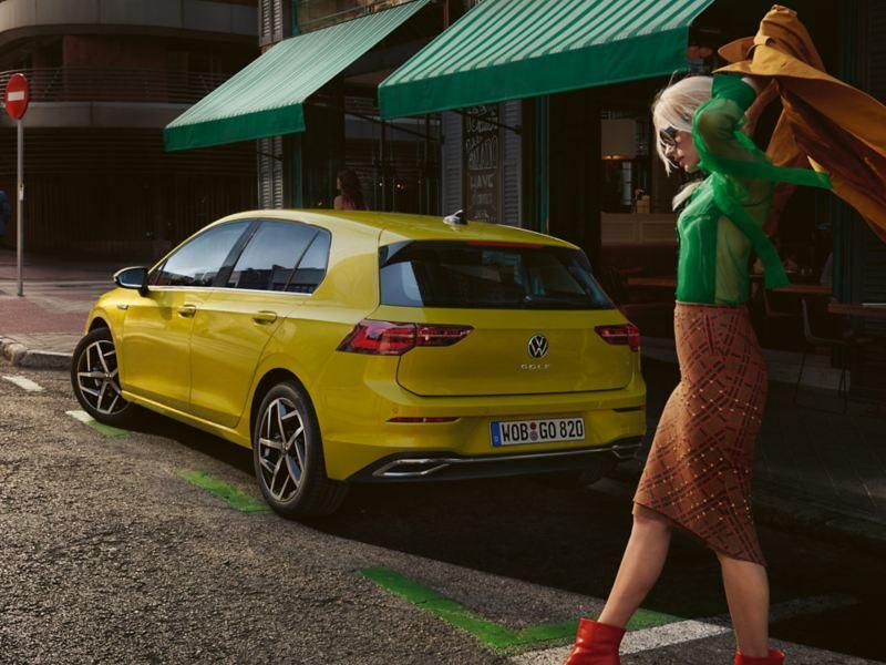 Skats uz VW Golf no aizmugures, tā priekšplānā sieviete velk mugurā mēteli