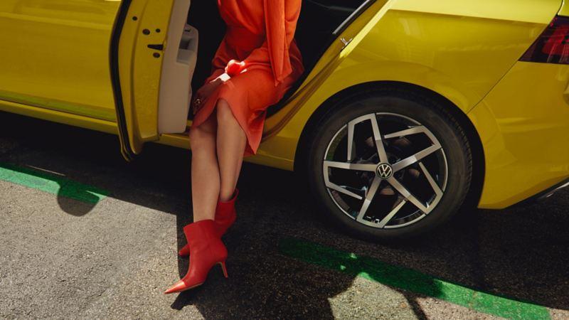 En kvinne sitter i døråpningen bak på VW  Volkswagen Golf