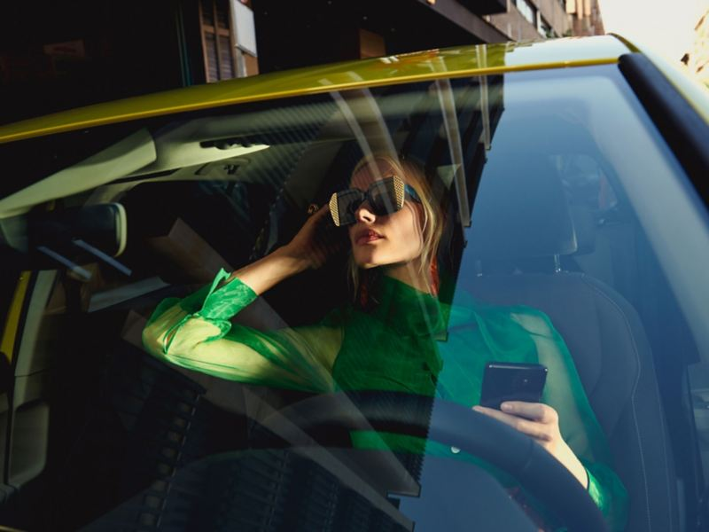 A woman sits on the driver's seat in the VW Golf and looks through the windshield