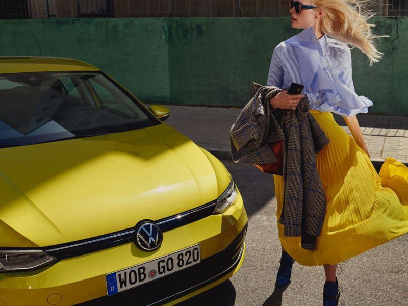 Sieviete stāv jaunā VW Golf priekšā