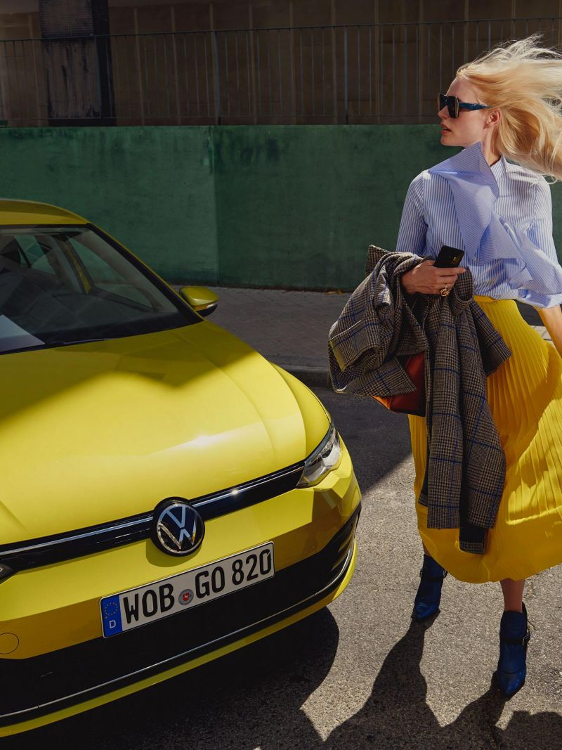 Μια γυναίκα στέκεται μπροστά από το Volkswagen Golf
