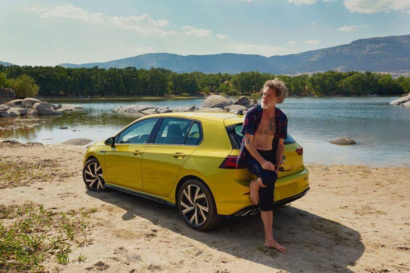 Man at the rear of the VW Golf, in the background a lake and mountains