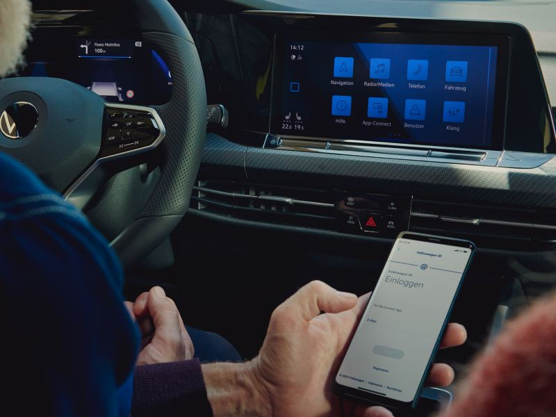 Man holds a cell phone in front of the display in the VW Golf