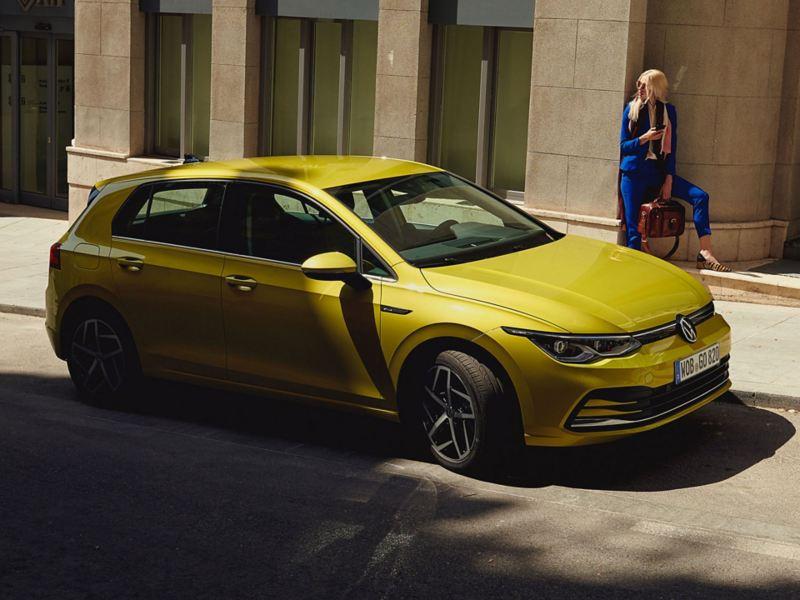 Nuevo VW Golf aparcado en la calle junto a una mujer
