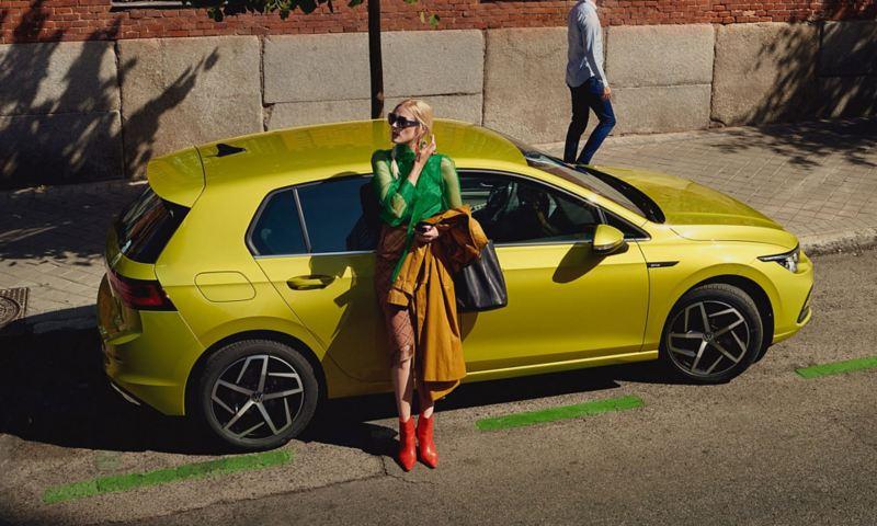 """""""VW Golf"""" stovi šalikelėje, moteris atsirėmusi į šonines dureles"""