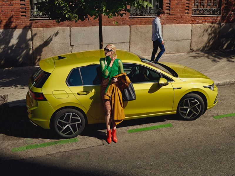 VW Golf novietots ielas malā, sieviete atspiedusies pret tā sānu durvīm