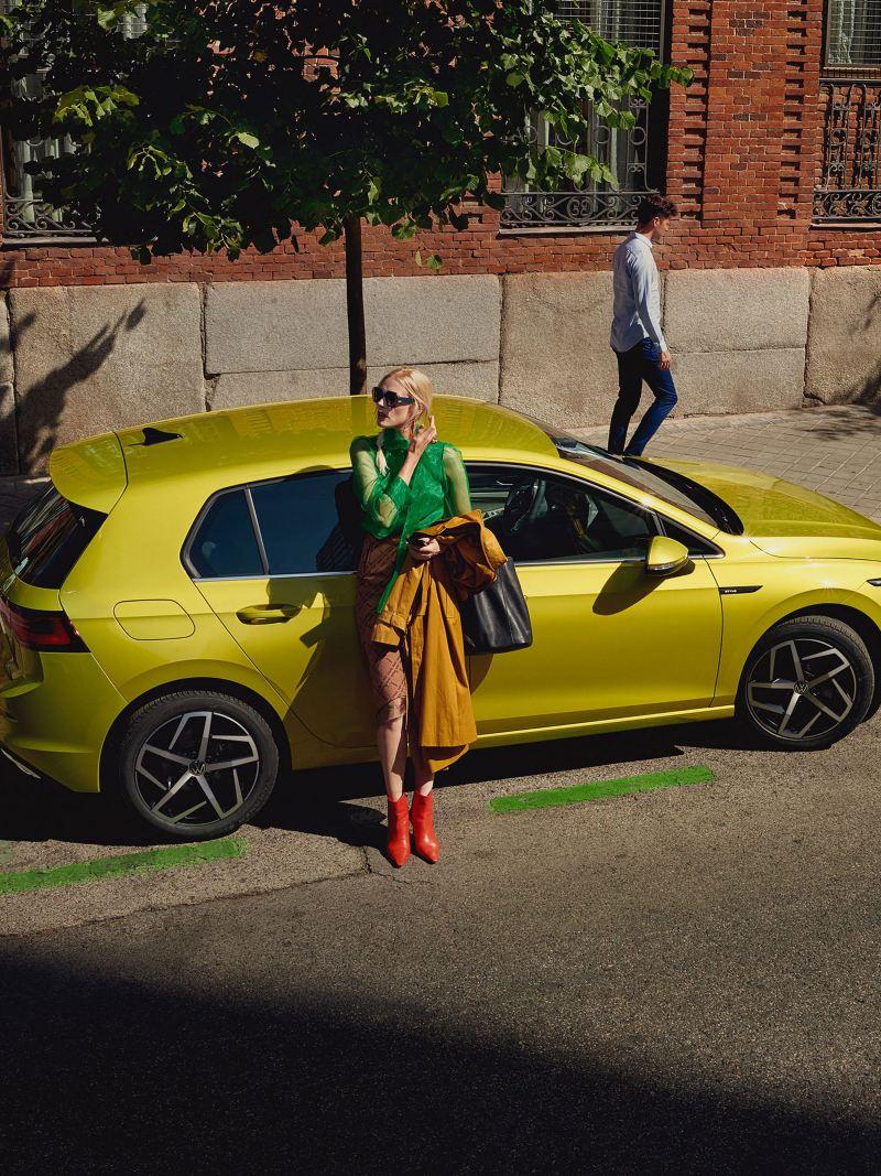 Tee äärde pargitud VW Golf, naine nõjatub vastu külgmist ust