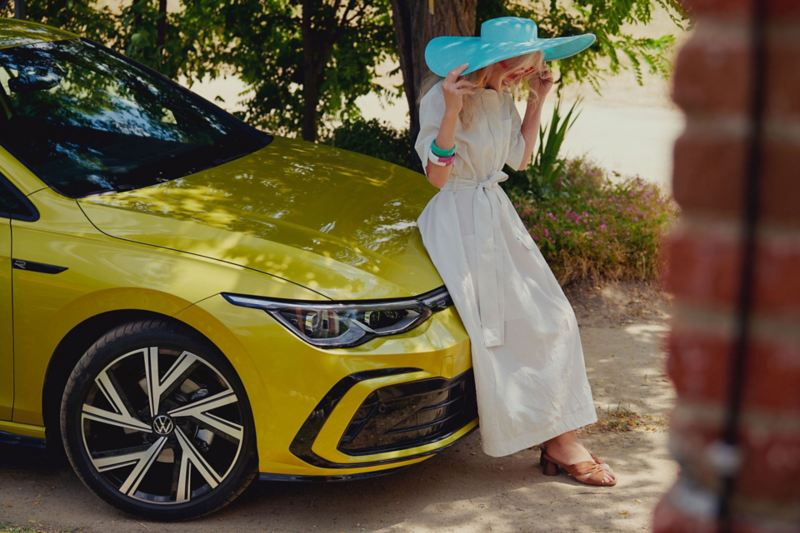 A woman with a white dress stands at the bonnet of the new VW Golf