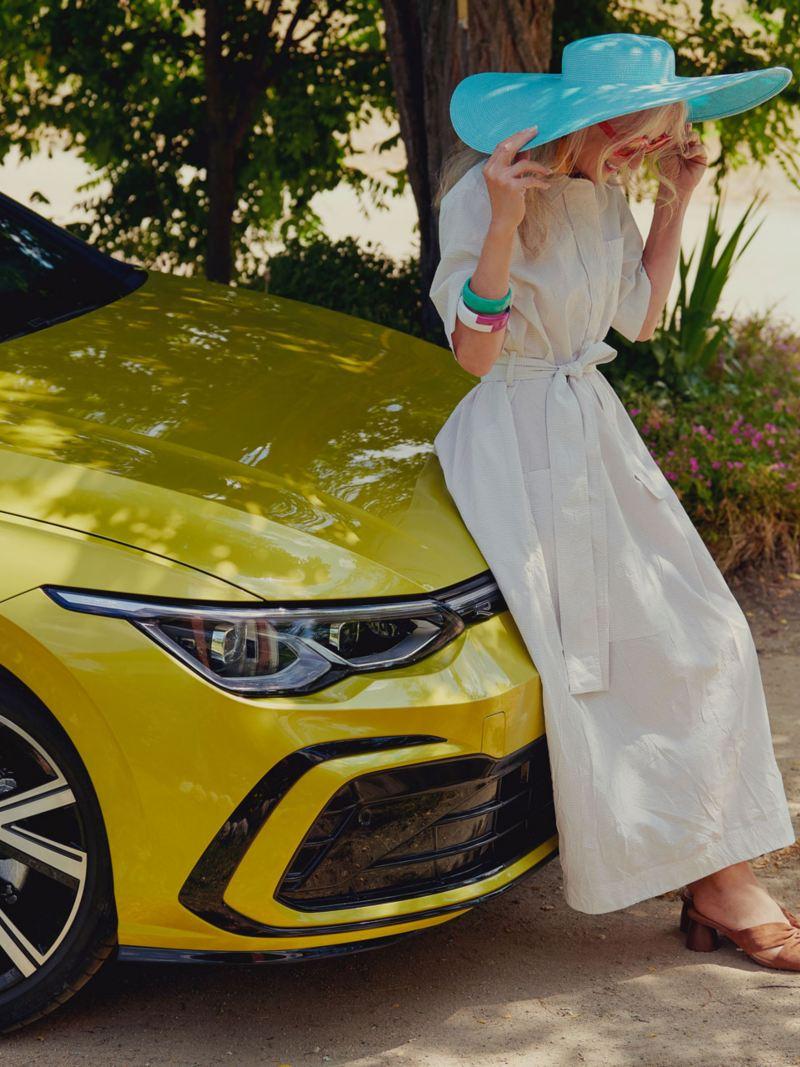 Une femme en robe blanche contre le capot de la Golf