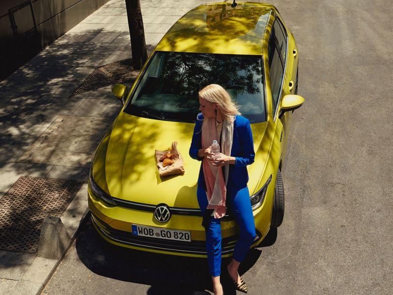 Mulher com croissants e água encostada ao capô do Volkswagen Golf