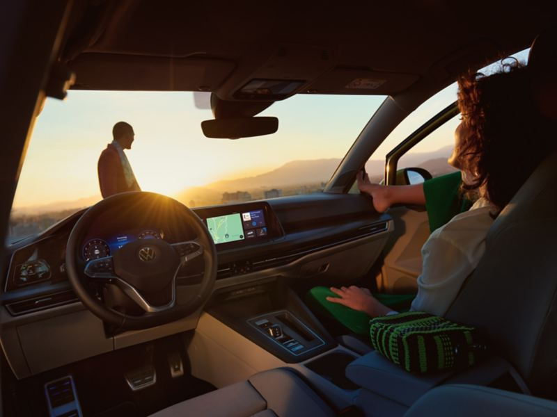Uma mulher está sentada de forma descontraída no lugar do passageiro da frente do VW Golf