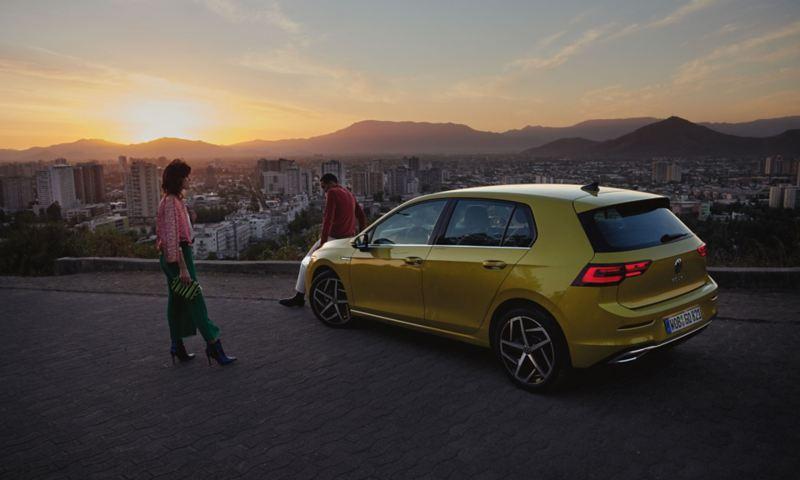 Vista lateral do VW Golf, no topo de uma montanha, em frente a um casal